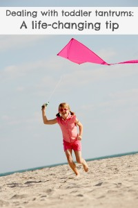 Girl running on beach with kite